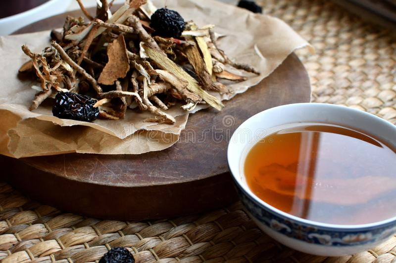 Chinese traditional medicine script. Side view. Chinese traditional medicine script. Herbal tea with jujubes, goji berries, gingseng roots and others on royalty free stock photo