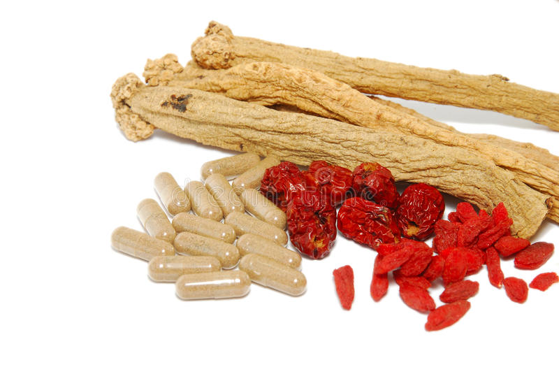 Chinese traditional medicine and Western medicine. Contrast or fusion of an assortment of Chinese traditional herbs and a pile of Western medicinal capsules stock images