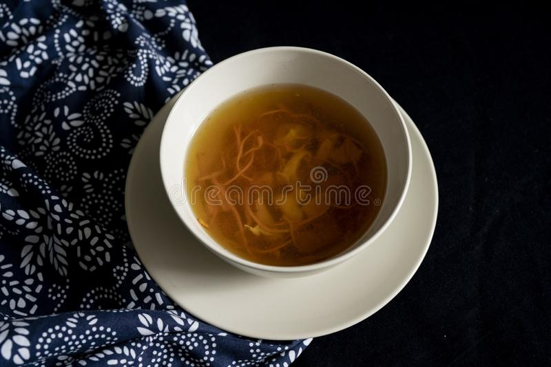 Chinese traditional nourishing health soup. A bowl of chinese traditional nourishing health soup, meat, cordyceps flower royalty free stock images