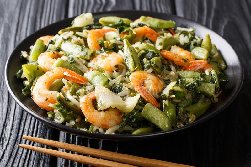 Chinese traditional Stir frying of shrimp, spinach, soy sprouts. Pea pods and pak choi close-up on a plate on the table. horizontal stock image