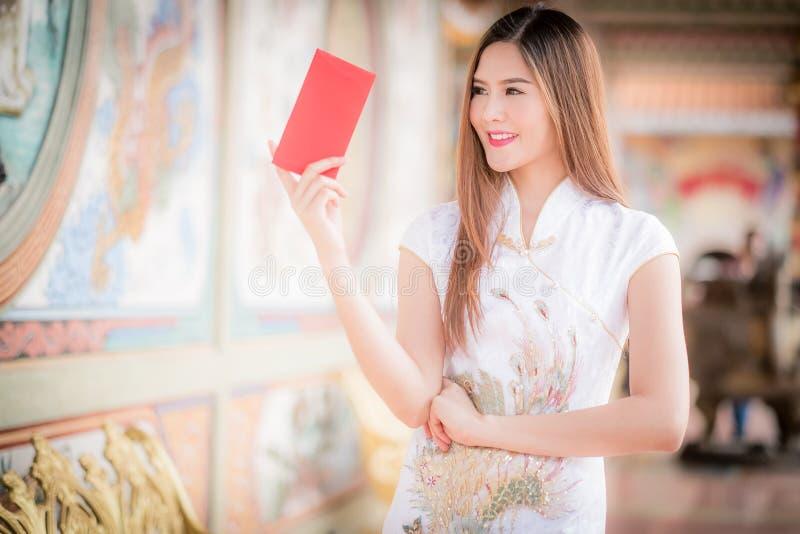 Chinese traditionele cheongsam van de vrouwenkleding en greep rode envelop royalty-vrije stock afbeeldingen