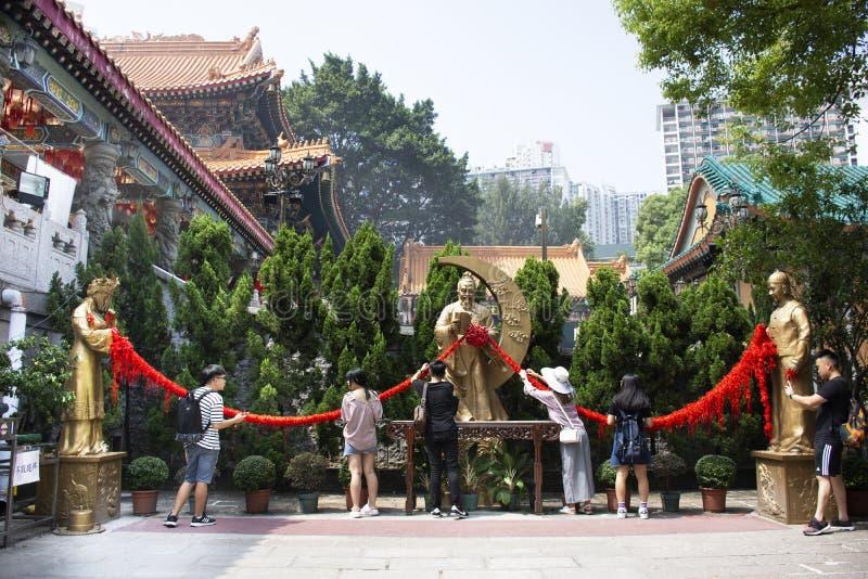 Chinese- und Ausländerleutereisebesuch und betenden Gott und Engel bei Wong Tai Sin Temple in Hong Kong, China respektieren stockbild