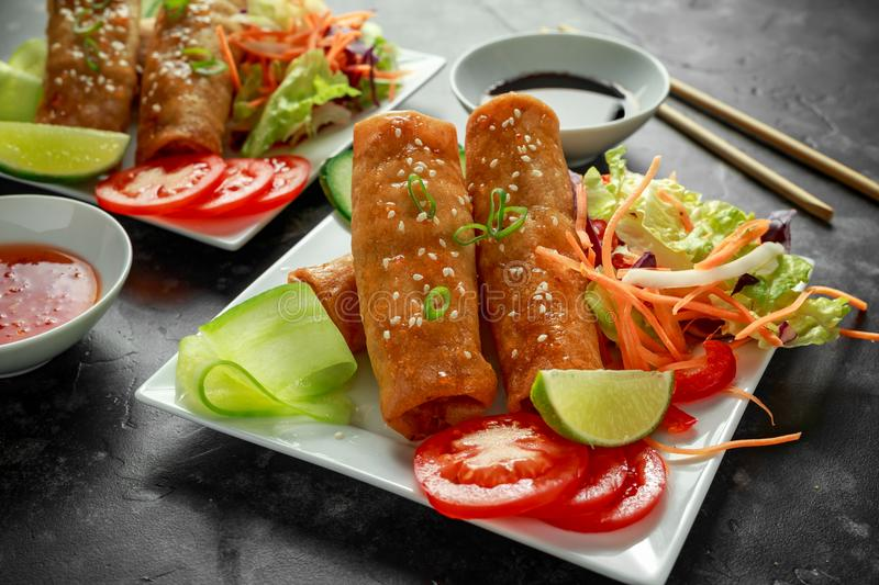 Chinese vegetable spring rolls garnished with fresh salad, lime wedges, sweet chilli sauce and soy sauce royalty free stock image