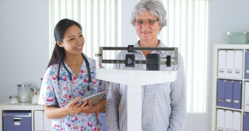 Chinese verpleegster die bejaarde patiënt wegen stock afbeelding