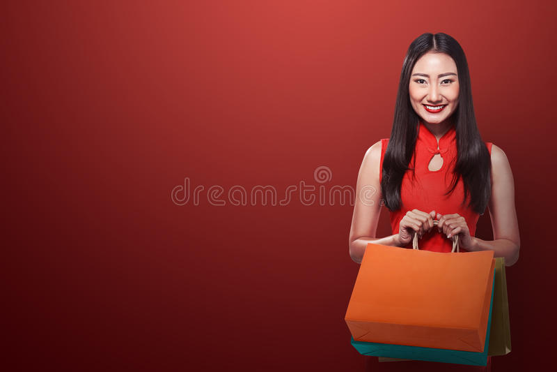 Chinese vrouw in de holding van de cheongsamkleding het winkelen zak royalty-vrije stock afbeeldingen