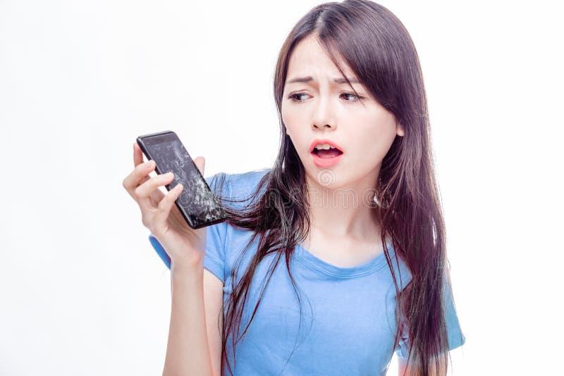 Chinese vrouw die bij gebroken celtelefoon staren stock fotografie