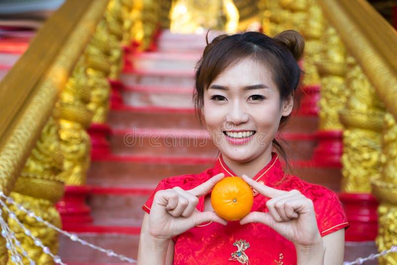 Chinese vrouw die traditioneel kostuum dragen tijdens Chinees Nieuw Stem vóór royalty-vrije stock foto