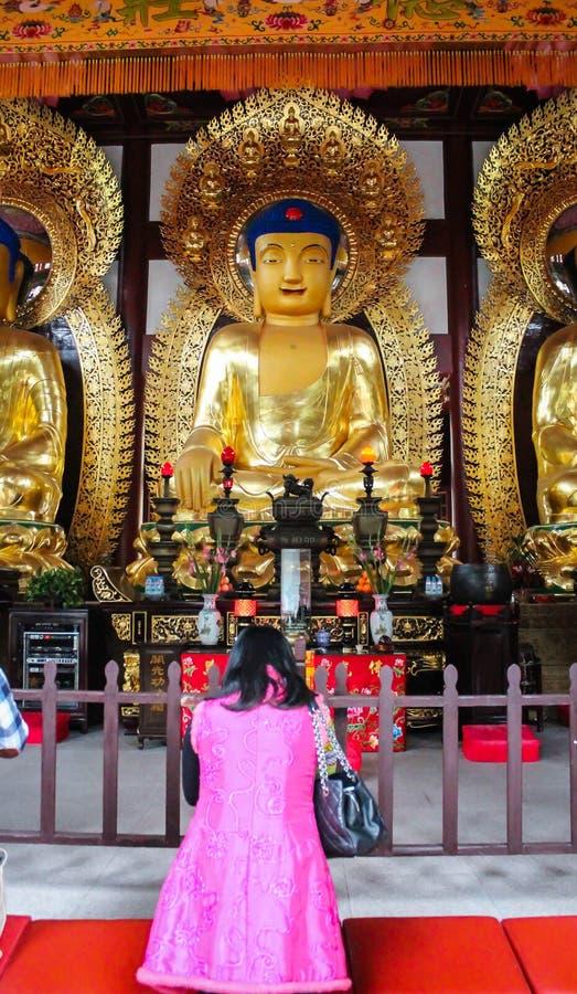 Chinese vrouw die voor het Standbeeld van Boedha bidden stock foto