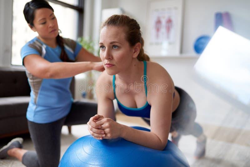 Chinese vrouwen persoonlijke trainer tijdens een trainingzitting met een aantrekkelijke blonde cliënt in een helder medisch burea royalty-vrije stock fotografie