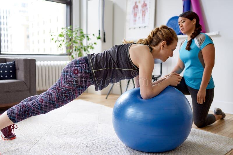 Chinese vrouwen persoonlijke trainer tijdens een trainingzitting met een aantrekkelijke blonde cliënt in een helder medisch burea stock foto's