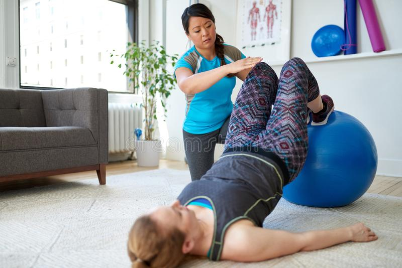 Chinese vrouwen persoonlijke trainer tijdens een trainingzitting met een aantrekkelijke blonde cliënt in een helder medisch burea stock foto
