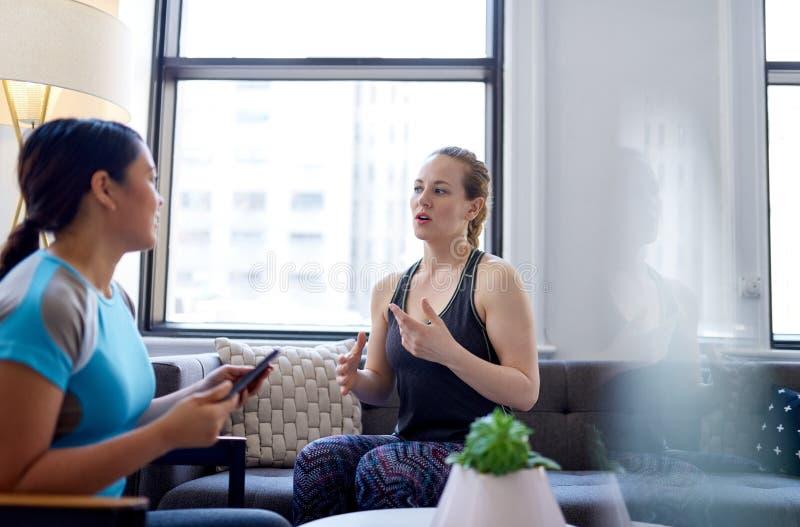 Chinese vrouwenfysiotherapeut die aan een medio-volwassen Kaukasische vrouwelijke patiënt spreken en nota's over een tablet nemen royalty-vrije stock foto