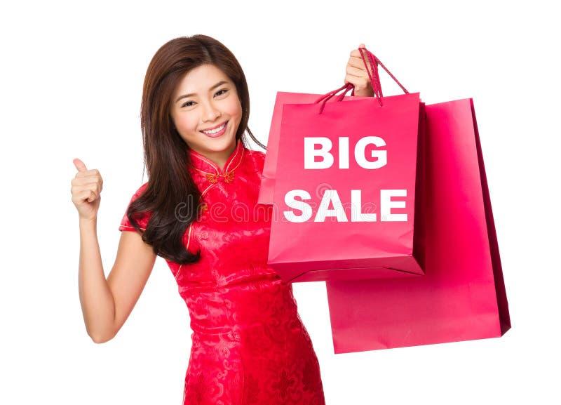 Chinese vrouwengreep met het winkelen zak en duim omhoog voor het tonen van bi stock afbeeldingen