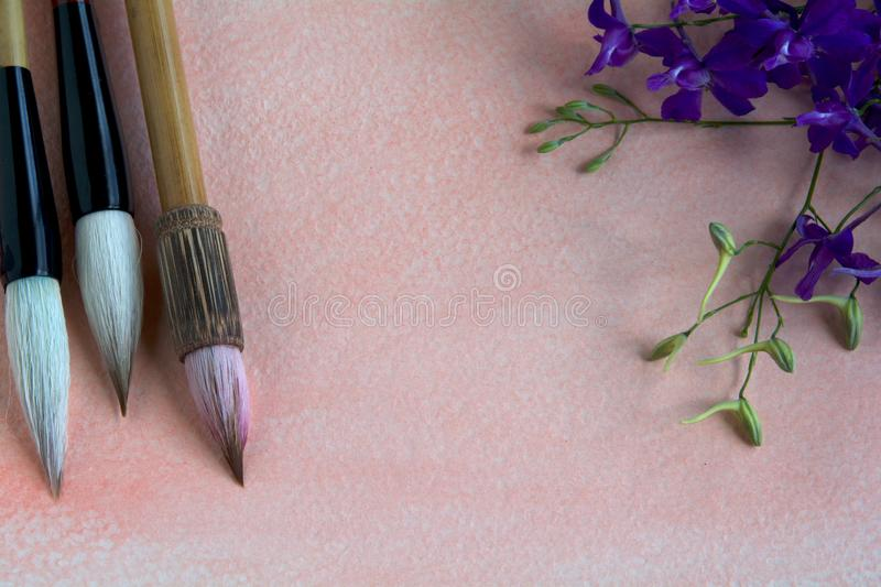 Chinese watercolor brushes on a pink-tinged watercolor sheet adorned with purple wildflowers.  royalty free stock image