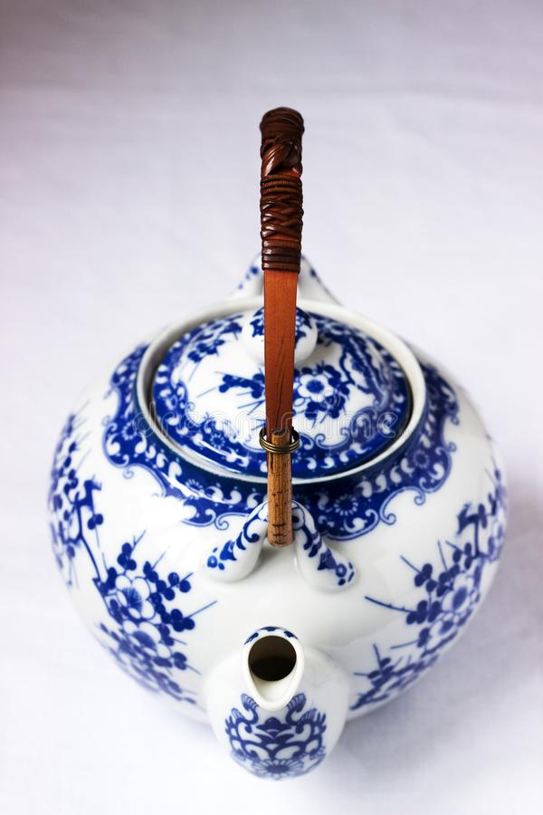 Chinese white porcelain teapot with bamboo handle and blue pattern on a white background. Selective stock photos