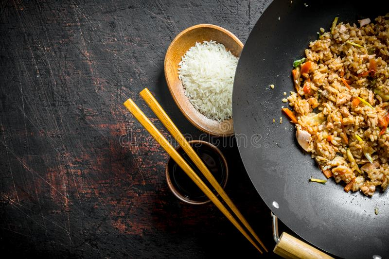 Chinese wok. Cooked rice in a wok pan and uncooked rice on a plate royalty free stock photos