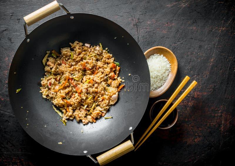 Chinese wok Gekookte rijst in een wok pan en ongekookte rijst op een plaat stock afbeeldingen