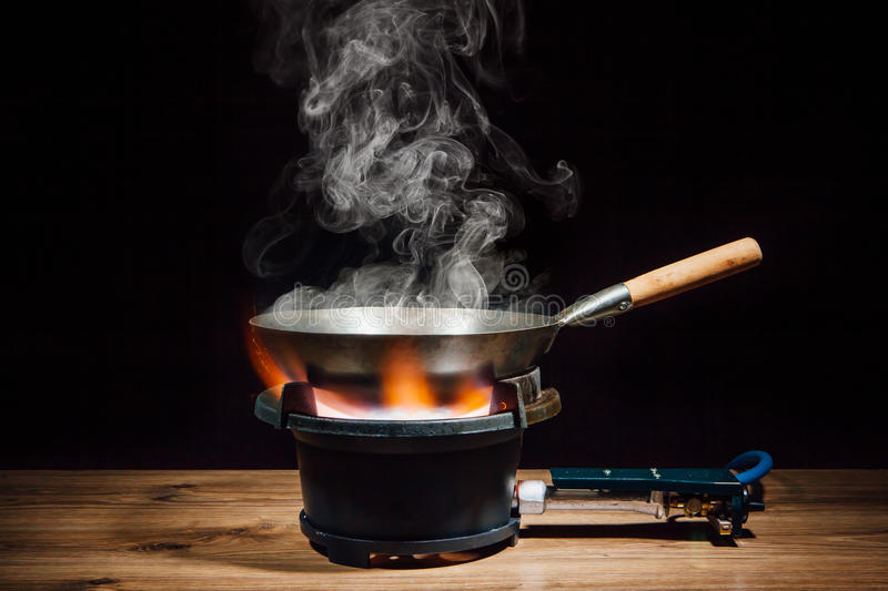 Chinese wok pan on fire gas burner royalty free stock photos