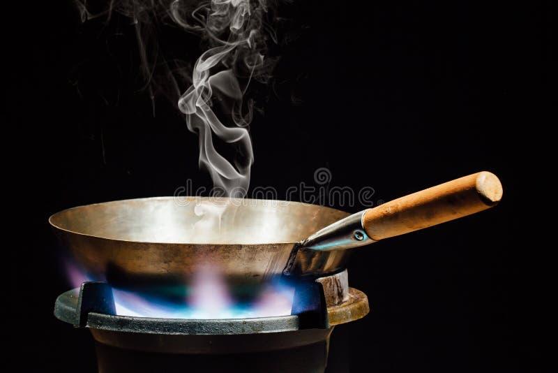 Chinese wokpan op brandgasfornuis stock afbeelding