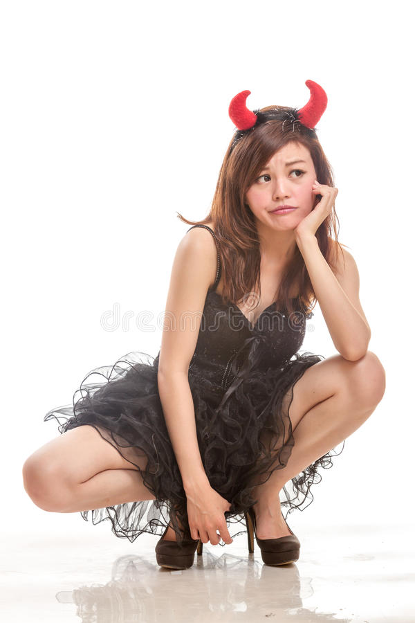 Chinese woman in black dress and devil horns squatting down look stock photo