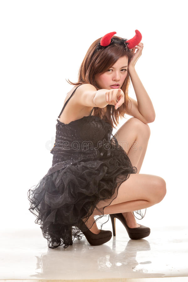 Chinese woman in black dress and devil horns squatting down pointing at camera royalty free stock photo