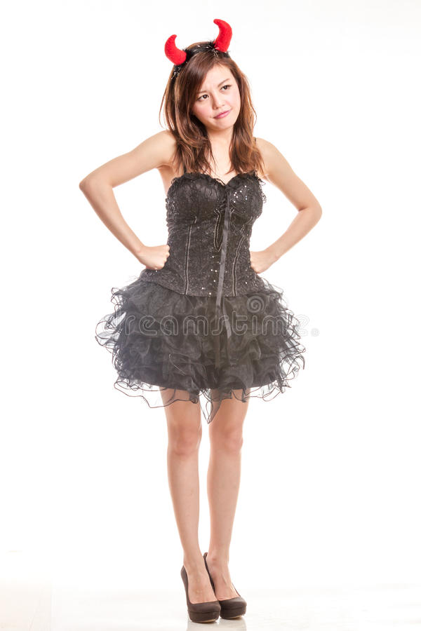 Chinese woman in black dress and devil horns standing with hands royalty free stock images