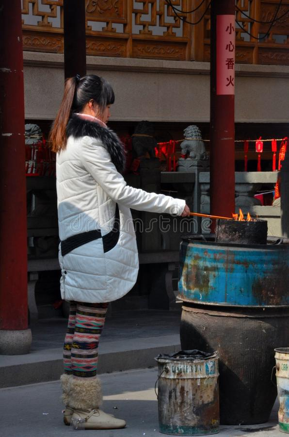 Chinese woman burns incense offering at Taoist temple royalty free stock image