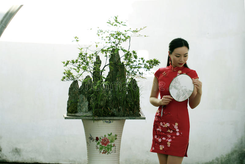 Chinese woman in cheongsam in Mudu ancient town by a bonsai trees and mountains. In Suzhou classical garden,Yan garden in Mudu old town, sweet smile royalty free stock photography