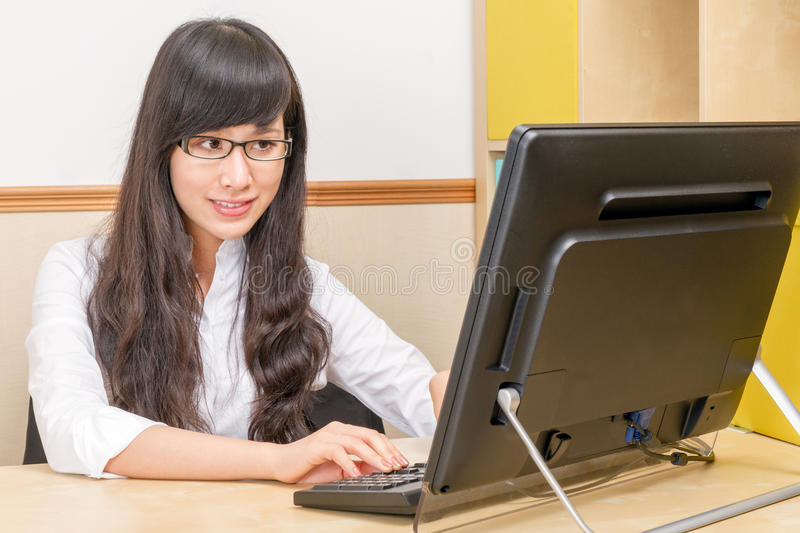 Chinese woman at desk typing on computer royalty free stock photography