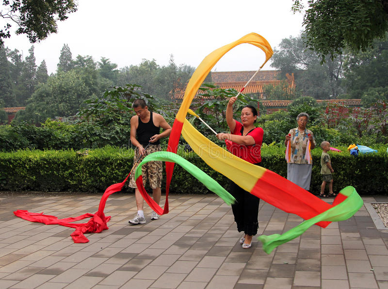 Chinese woman doing gymnastics with ribbons in Jingshan park royalty free stock images