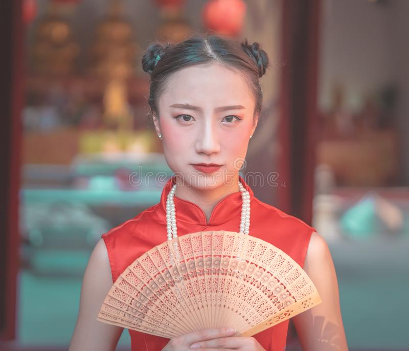 Chinese woman holding a wooden fan for chinese new year fashion concept royalty free stock images