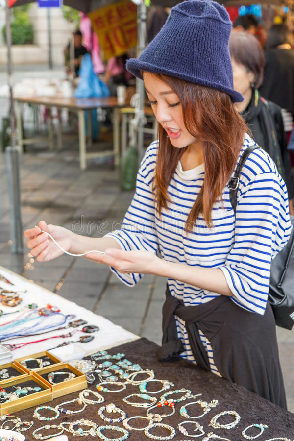 Chinese woman looking at jewelry at market stock image