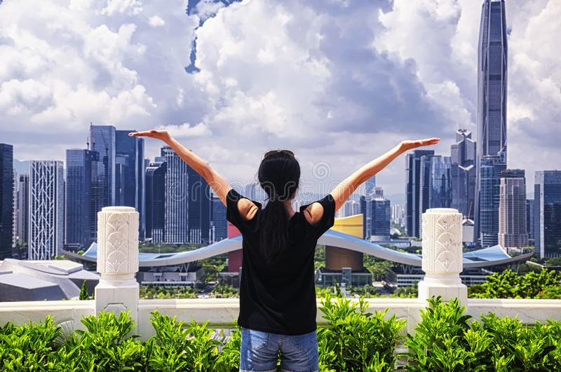 Chinese woman in shenzhen china. A chinese woman looking out over the city of Shenzhen China on a sunny blue sky day from lianhuashan park stock photography