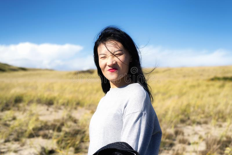 Cape Cod National Seashore Nature woman. A chinese woman making a funny face outside on a sunny windy day on the cape cod national seashore in Truro stock photo