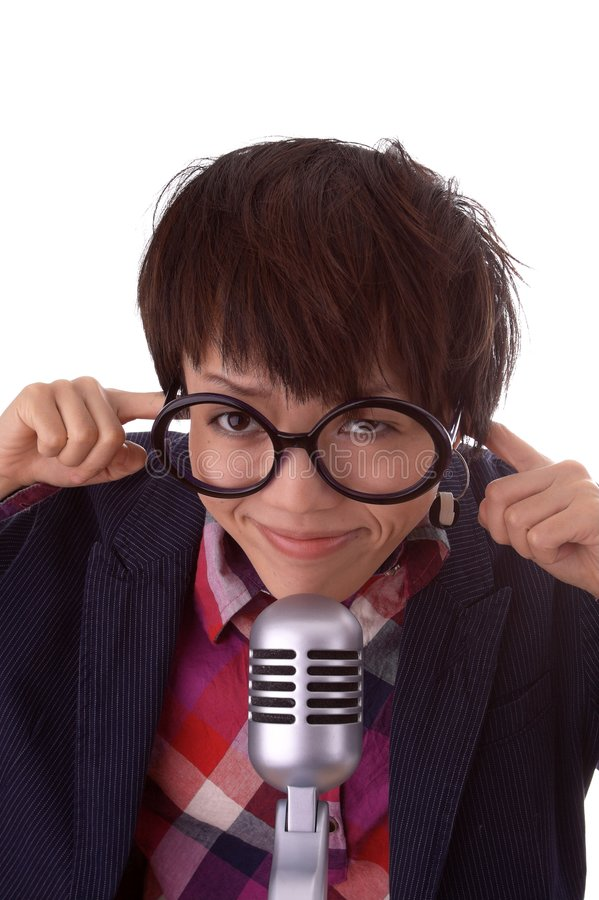 Chinese Woman and Microphone. Smiling young Chinese woman wearing large, round glasses with her fingers in her ears, in front of a microphone. Isolated on a royalty free stock images
