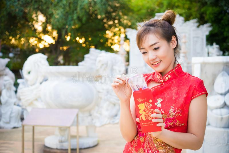 Chinese woman pulling, holding money note from envelope with hap stock photo