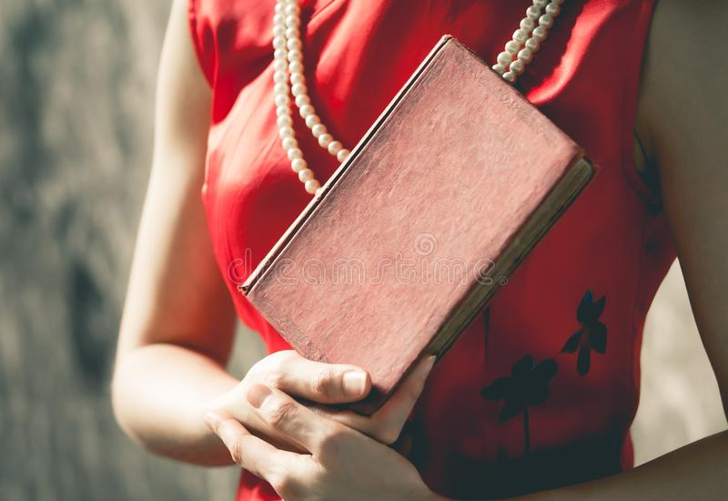 Chinese woman in red holding a blank cover book for mock up stock photo