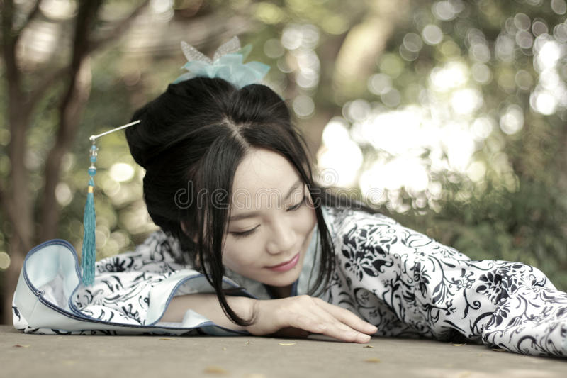Chinese woman in traditional Blue and white Hanfu dress Climb over the stone table. Chinese woman in traditional Hanfu dress Climb over the stone table at Qiyuan royalty free stock photo