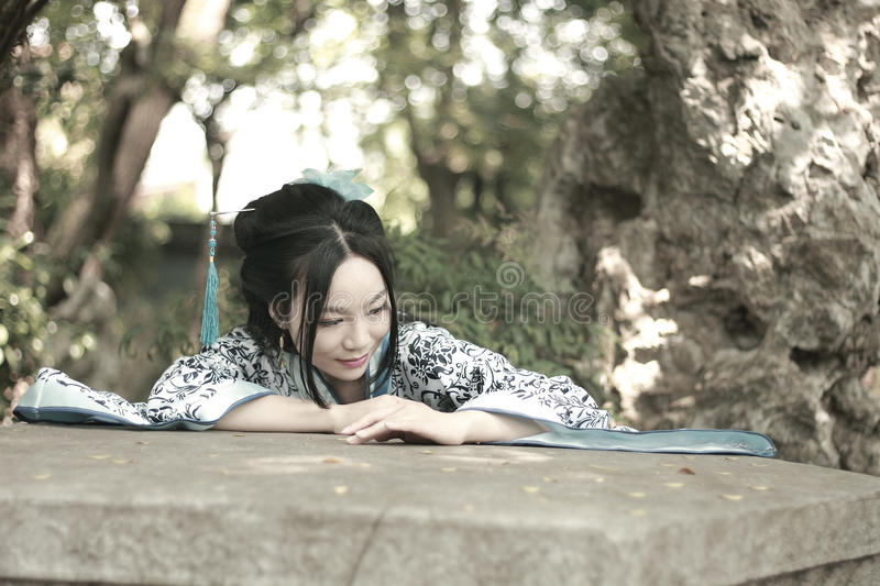 Chinese woman in traditional Blue and white Hanfu dress Climb over the stone table royalty free stock images