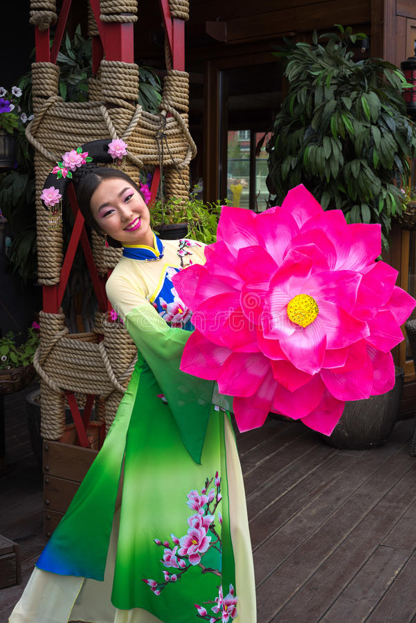 Chinese woman. Woman in traditional chinese dress with pink flower royalty free stock photos