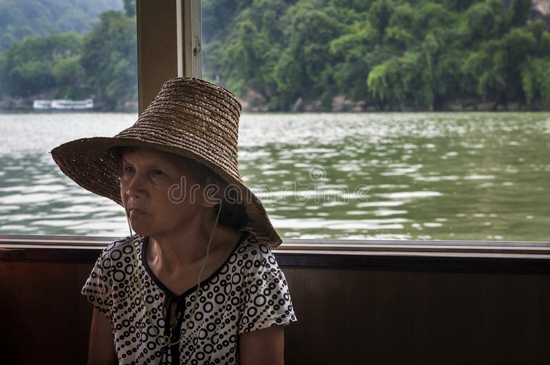 Chinese woman traveling in a boat in the Li River near the town of Yangshuo stock photography