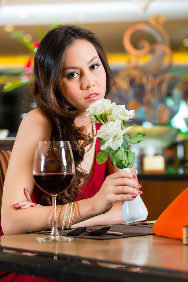 Chinese woman waiting in restaurant for date stock photography