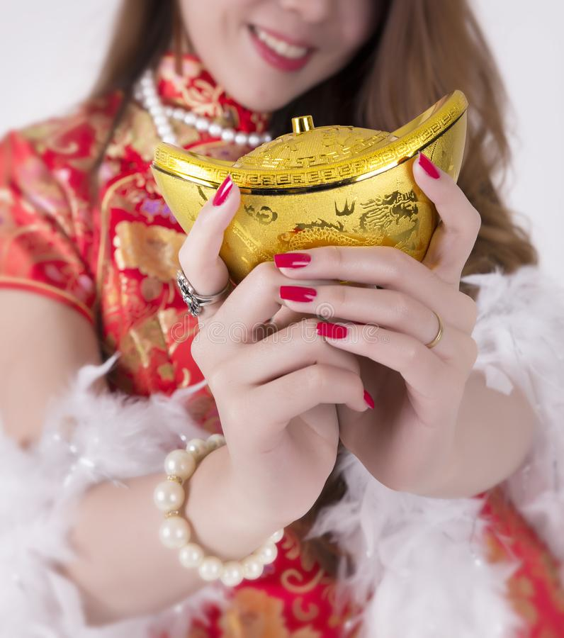 Cheongsam dress. Chinese woman wear cheongsam and holding gold ingot, asian, , clothing, greeting, oriental, spring, fortune, red, new, pose, happiness, culture stock photos