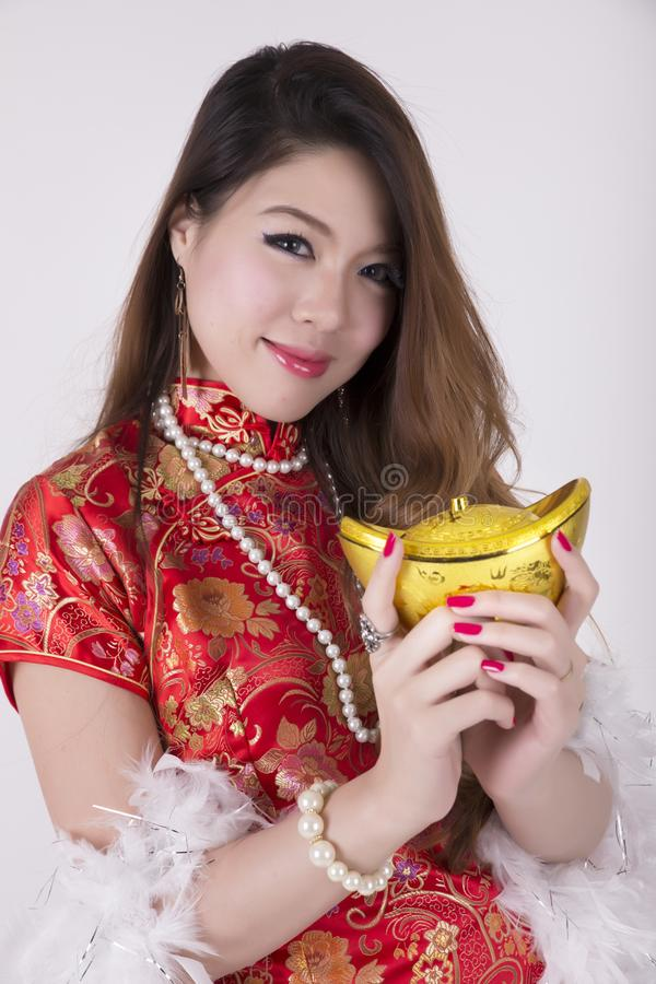 Cheongsam dress. Chinese woman wear cheongsam and holding gold ingot, asian, isolated, clothing, greeting, oriental, spring, fortune, red, new, pose, happiness stock image
