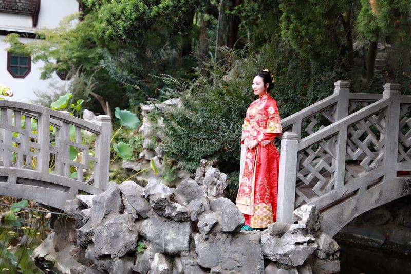 Chinese woman wearing a typical Chinese bride`s silk red dress, adorned with golden phoenix and drag on the bridge royalty free stock photo
