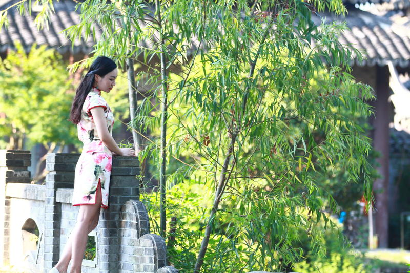 A Chinese woman wears Cheongsam in the water park of Shanghai royalty free stock image