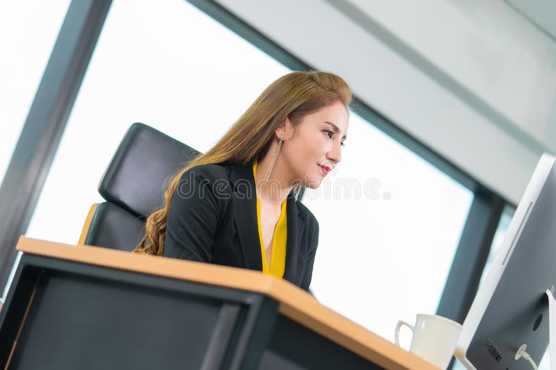 Chinese woman working with computer laptop in modern city office stock photo