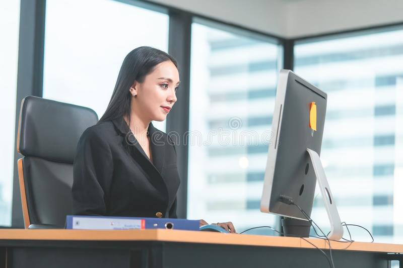 Chinese woman working with computer laptop in modern city office alone looking at computer monitor stock photography