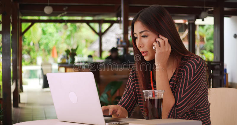 Chinese woman working on her paper outside cafe.  royalty free stock photos