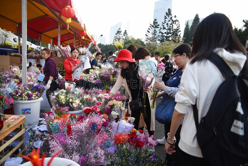 Chinese women are buying flowers at the Chinese new year market royalty free stock image